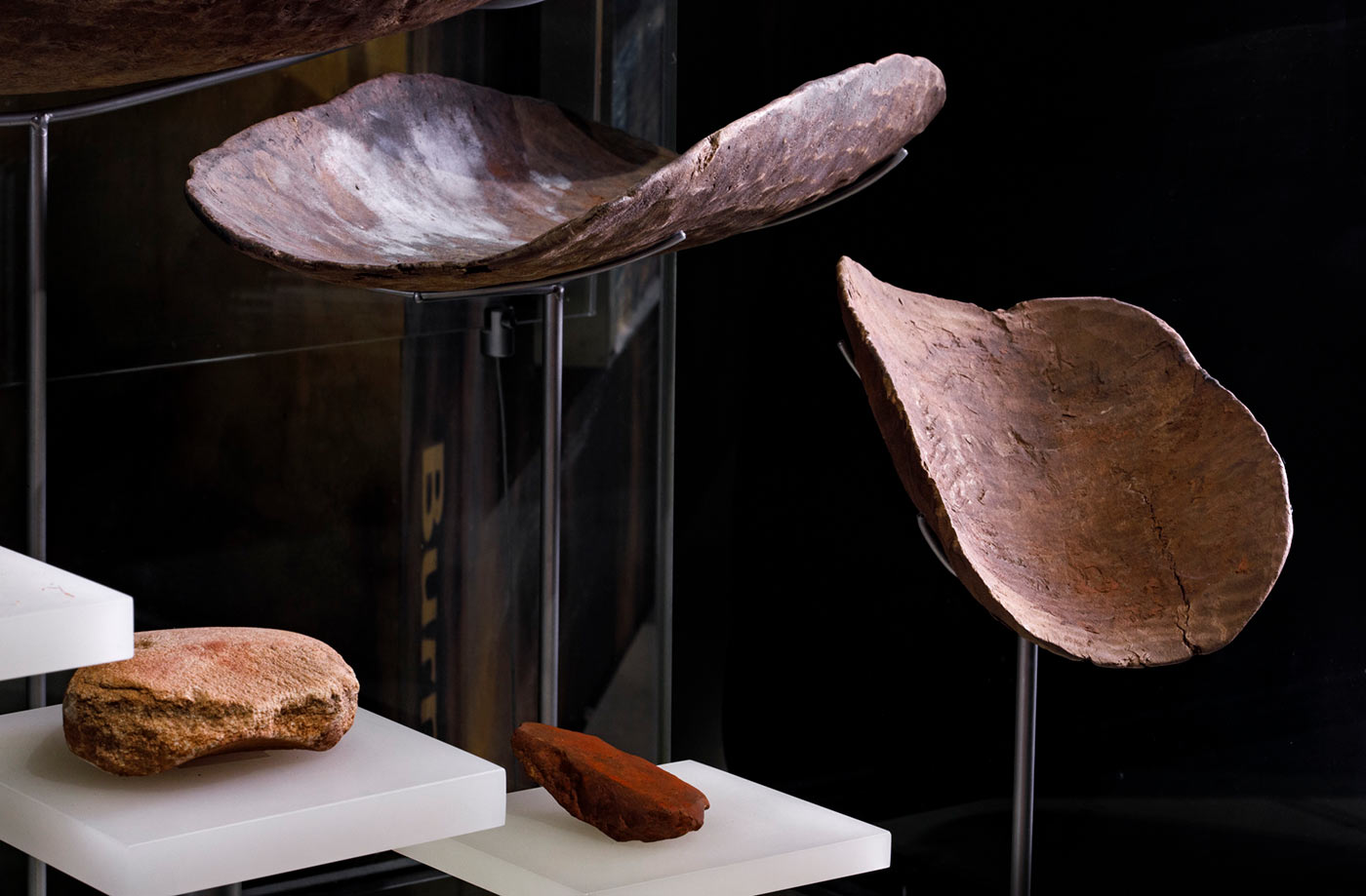 Museum display showing two shallow timber vessels above two grinding stones. - click to view larger image