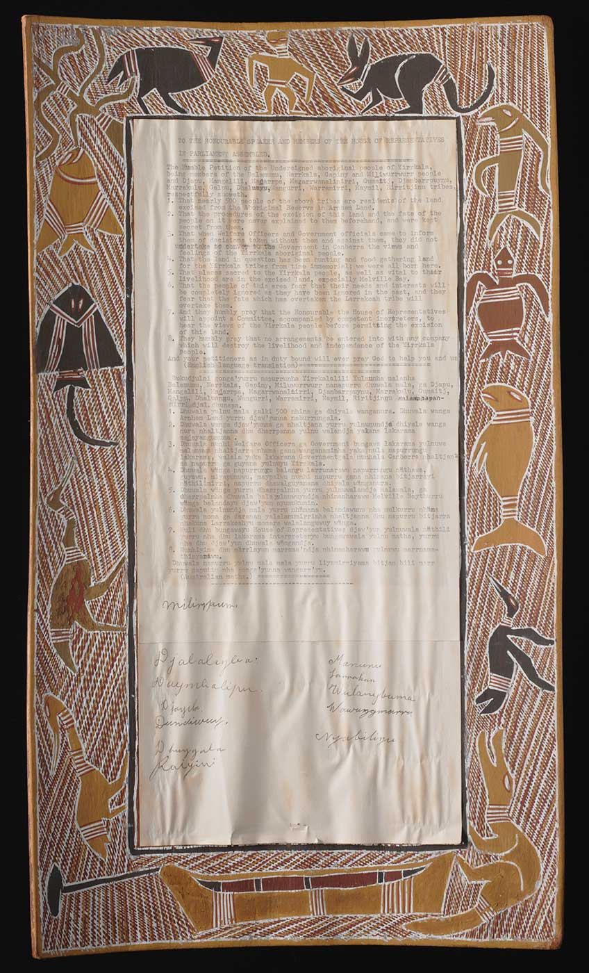 A rectangular bark painting that forms a border around a typed petition on paper. The bark is painted with yellow, white, brown, red, and black ochre. The border depicts a man, a kangaroo, a turtle, a dugong, a crocodile, a stingray, fish, several birds, and a canoe on a background of cross-hatching. The petition is stuck to the centre of the bark and has a heading that reads 'TO THE HONOURABLE SPEAKER AND MEMBERS OF THE HOUSE OF REPRESENTATIVES / IN PARLIAMENT ASSEMBLED...'. There are two blocks of text underneath the heading. The first block of text is in English and begins 'The humble petition of the undersigned aboriginal people of Yirrakala...' The second block of text is in an Australian Aboriginal language. Each lists eight points. There are 12 handwritten signatures below the typed text. The paper is yellowed with some brown staining and it is wavy and wrinkled in places. There are two very small tears at the bottom of the paper.