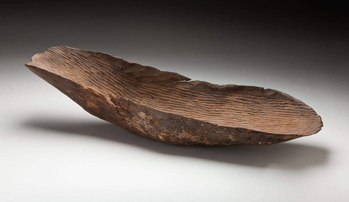 A carved wooden coolamon with an oval like shape. The wood has been carved to form a concave shape. The two ends are curved and it has parallel sides. The wood is chipped along the edges. The surface of the interior has been fluted whilst the outside shows adze markings. A hole has been drilled towards one end. - click to view larger image