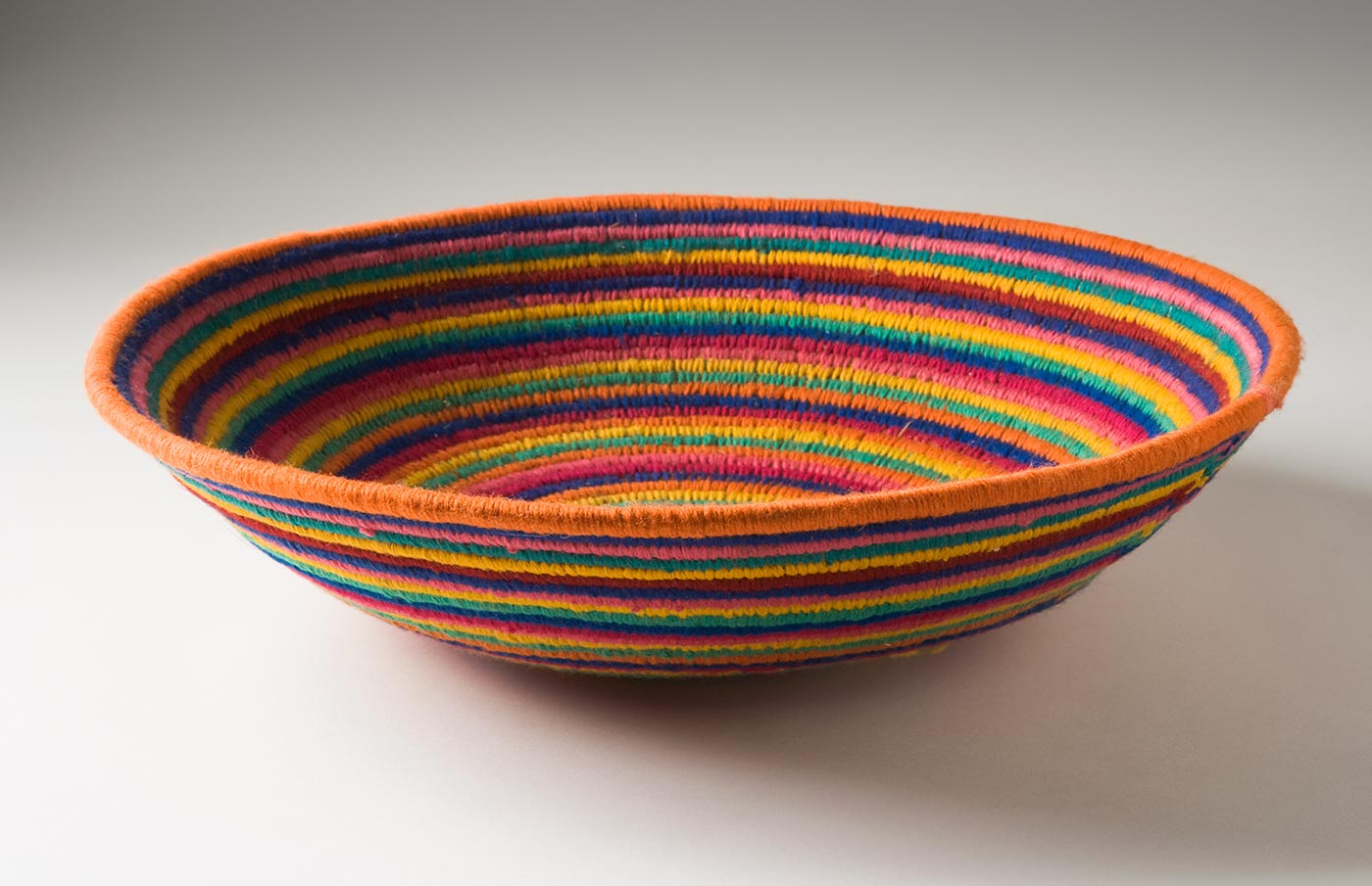 A multicoloured circular coiled yarn and plant fibre bowl-shaped basket. The centre of the basket is in pale pink yarn followed by horizontal stripes of yarn in lavender, pink, green, yellow, orange, blue and dark pink. - click to view larger image