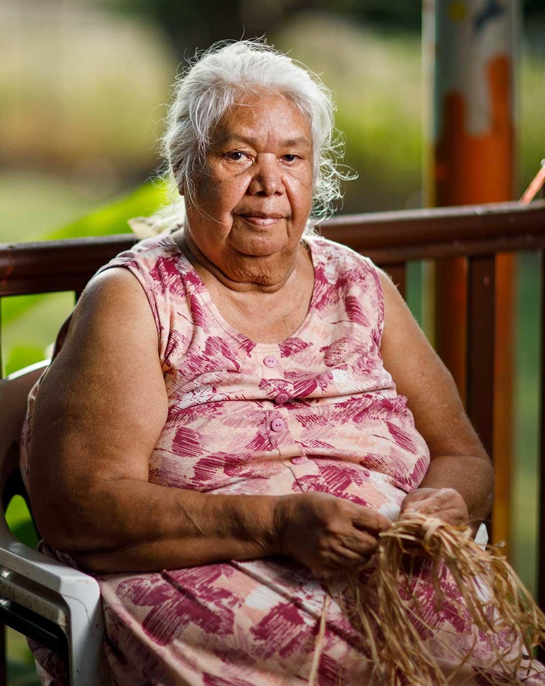 Colour photograph of an elderly woman sitting and weaving with natural fibres. - click to view larger image