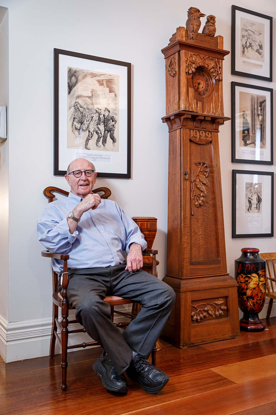 Trevor Kennedy sitting on a chair next to a longcase clock. - click to view larger image
