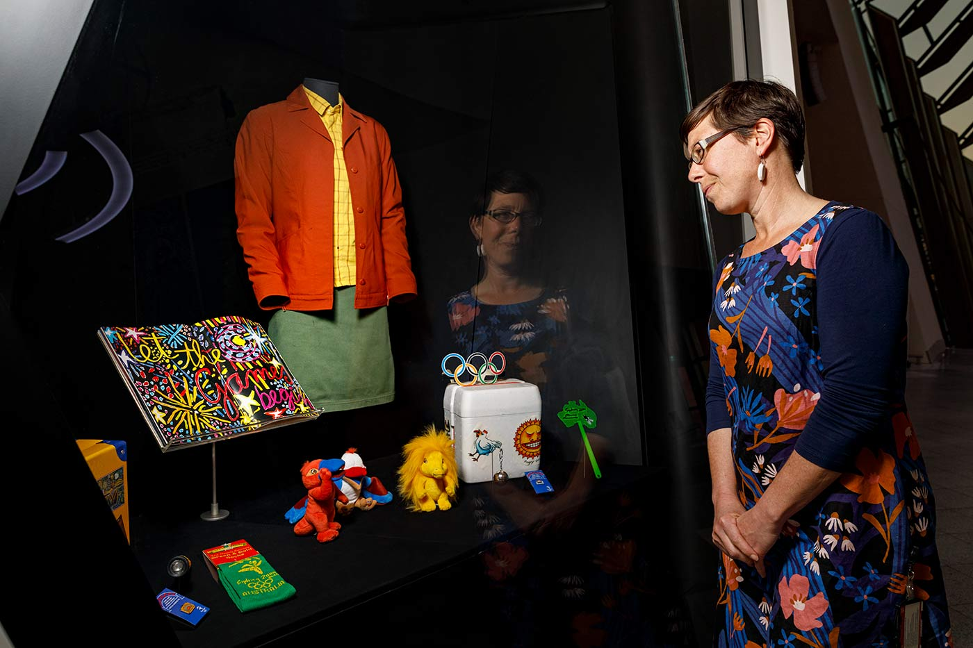 A female curator is looking lovingly at an exhibition display featuring objects from the Sydney Olympics.