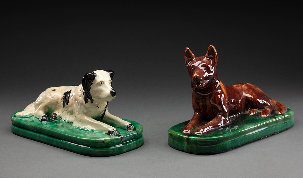 Two painted ceramic door stops in the shape of sitting dogs. The dog on the left has a black and white coat. The dog on the right is dark brown, with ears pricked. - click to view larger image