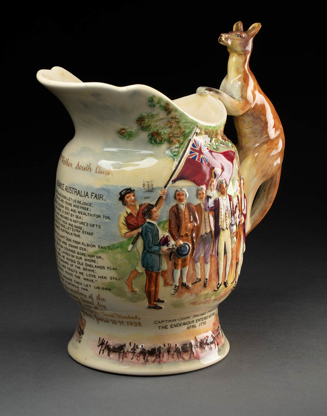 Fielding's Crown Devon earthenware 'Advance Australia Fair' musical jug which features relief moulding with a handle in the shape of a kangaroo. The jug has a painted scene of ships and a boat entering Botany Bay with Aboriginal men brandishing spears in their direction. Text below this reads, 'THE BLACKS THREW SPEARS AT COOK'S MEN.' There is also an image of Captain Cook raising his hat. He is surrounded by his men, one of whom is holding a red ensign. Text below this reads, CAPTAIN COOK TAKING POSSESSION. THE ENDEAVOUR ENTERED BOTANY BAY IN APRIL 1770'. The jug features the first and second verse of the poem 'Advance Australia Fair'. Text inscribed at the base in gilded lettering reads, 'Presented to the members of the Australian Touring Team by A. Ross. Fielding, on the occasion of the first test match at Nottingham, June 10.14.1938, C. W. Walker, South Aust.' Beside this is an untitled depiction of a drover's dray pulled along by a bullock team. The base is filled in with a wooden plate which has a winding mechanism set into it. The edge of the base has black text that reads 'CROWN DEVON / FIELDINGS / MADE IN ENGLAND'. - click to view larger image