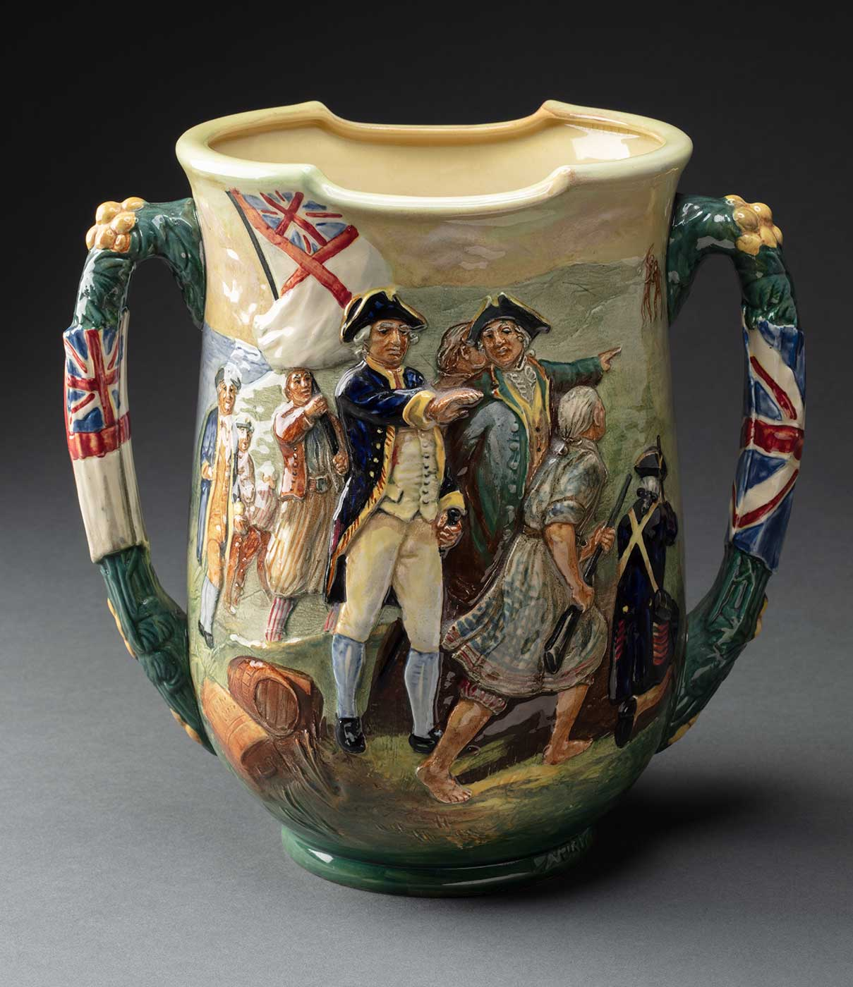 Royal Doulton loving cup (with two handles) depicting a scene of the early Australian colony. One one side Captain Cook and eight other men are shown in relief, with two figures of Indigenous men painted in the background. On the other side a sailing ship and two rowboats are shown with four figures on the shore in the foreground and several figures with the rowboats. Flags are depicted on the handles. The underside is stamped with 'Captain Cook / The Greatest Navigator / ... / Through storm & shine / alone on unknown - / seas. The Endeavour / anchored in Botany Bay / ub tge tear if iyr Kird / 1770' and 'The production of this cup / is limited to 350 / no. 215'. The trademark stamp reads 'Made in England / Royal Doulton / Registered / in Australia / No. 10610'. - click to view larger image