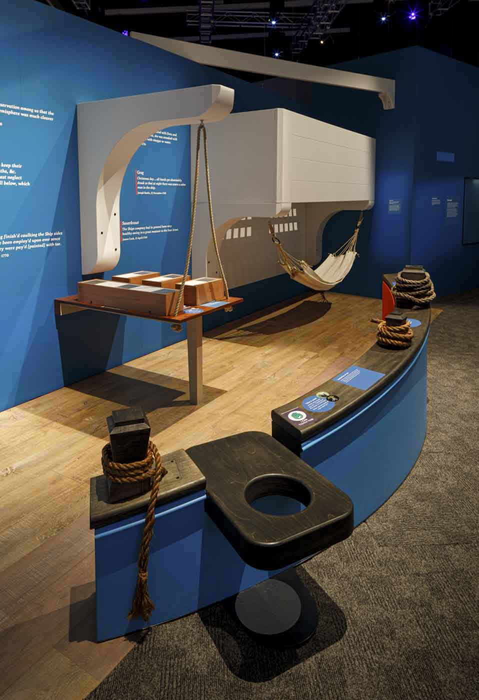 Interior view of a museum exhibition with a canvas hammock, ropes tied around bollards and a timber toilet seat. - click to view larger image