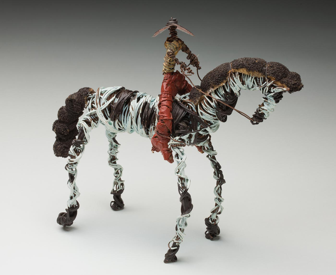 Bush toy consisting of a figure on a black and white horse made from painted coiled wire and fabric. - click to view larger image