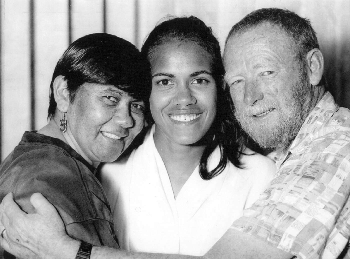 Black and white photograph of Cathy Freeman posing with her mother and stepfather. - click to view larger image