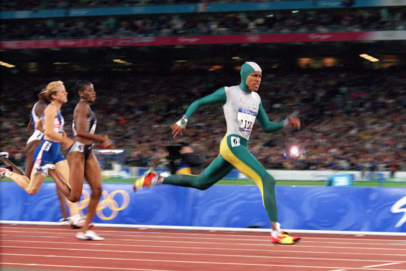 Cathy Freeman sprinting ahead of other athletes on a race track.