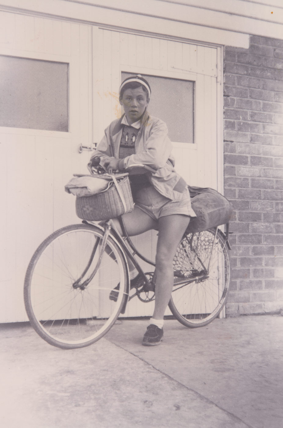 A black and white photo of Reima Miezitis with her bicycle. - click to view larger image