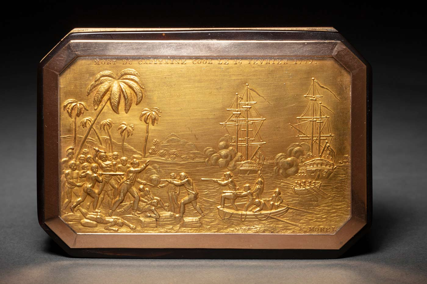 Tortoiseshell snuff box, incorporating a gold plaque on the lid that shows the death of Captain Cook at Kealukakua Bay in 1779, with boats on the harbour in the background. Relief text across the top of the gold plaque reads 'MORT DU CAPITAINE COOK LE 16 FEVRIER 1779'. The artist's signature 'Morel' appears at the bottom right corner.