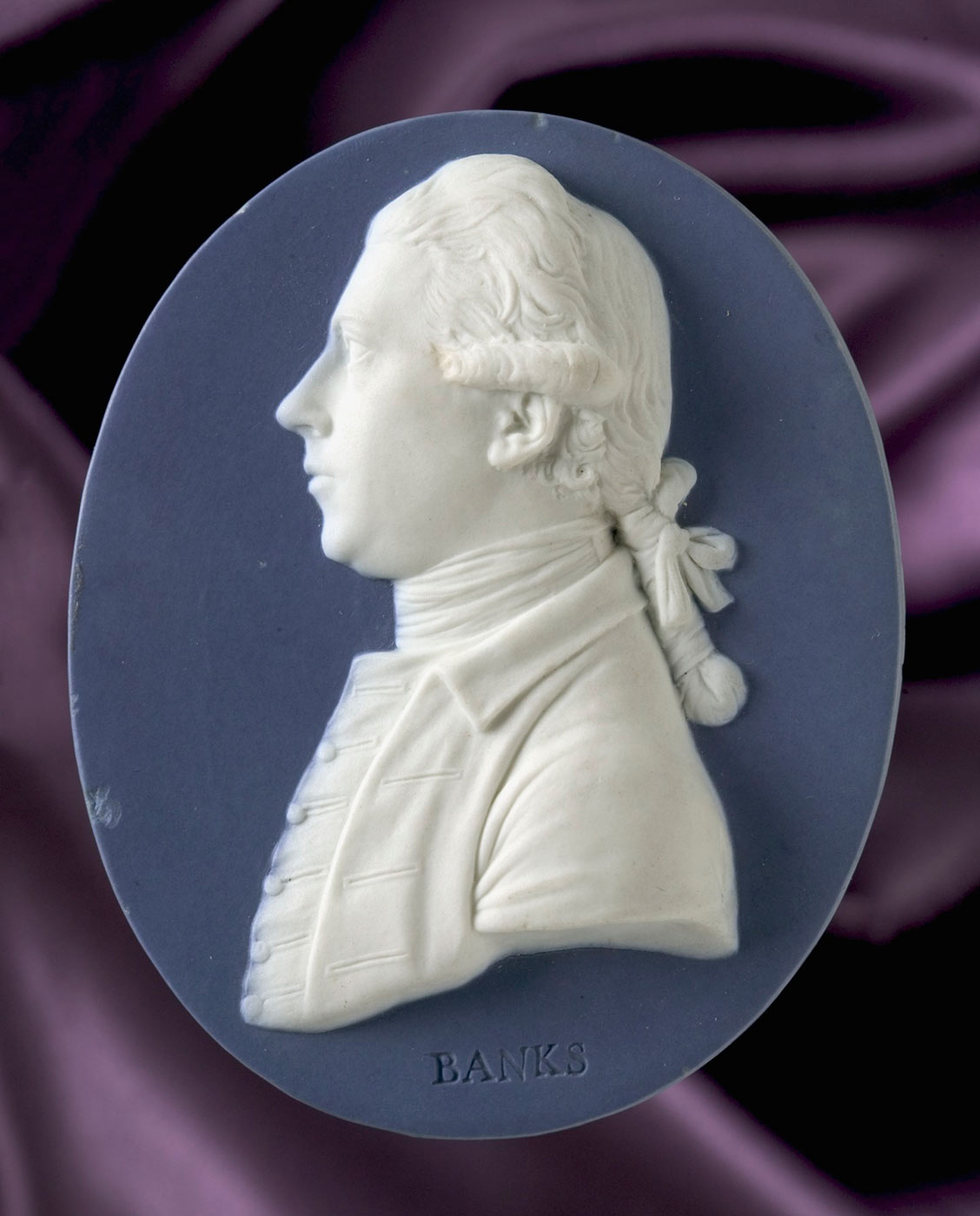 Oval blue jasper portrait medallion of Sir Joseph Banks, featuring a white profile bust in relief on a blue background. Below the bust imprinted into the ceramic is the text 'BANKS'. - click to view larger image