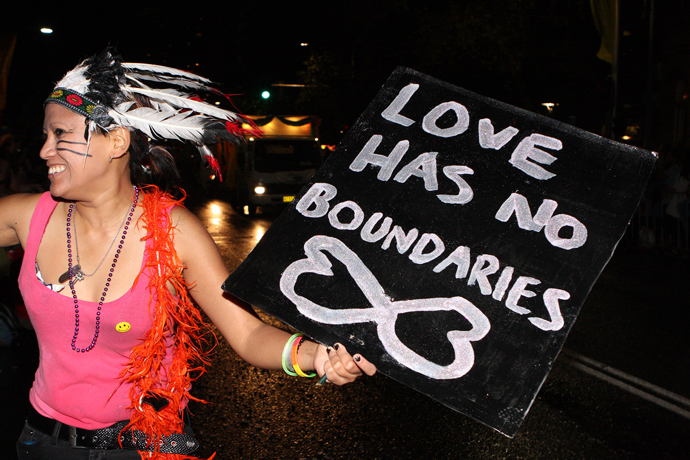 Woman in feathered headdress holding placard saying 'Love has no boundaries'.