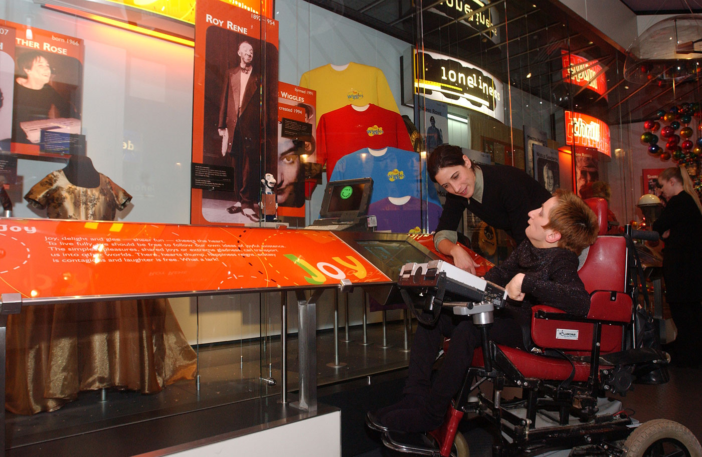 A woman talking to another woman in a wheel chair, in front of a large display cabinet with various objects. - click to view larger image