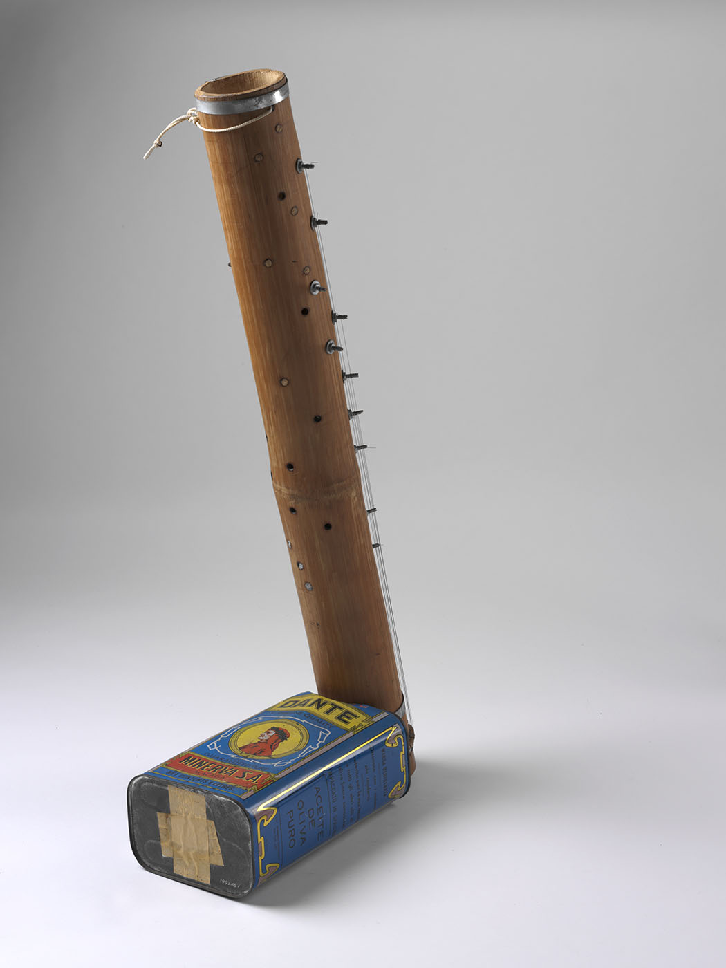 A musical instrument consisting of a bamboo tube with keys and strings down the sides and a blue olive oil tin at the base. - click to view larger image