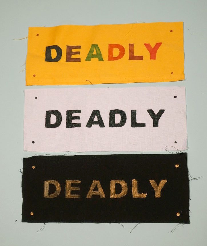Three pieces of fabric with the word Deadly printed and painted on each in different colours.