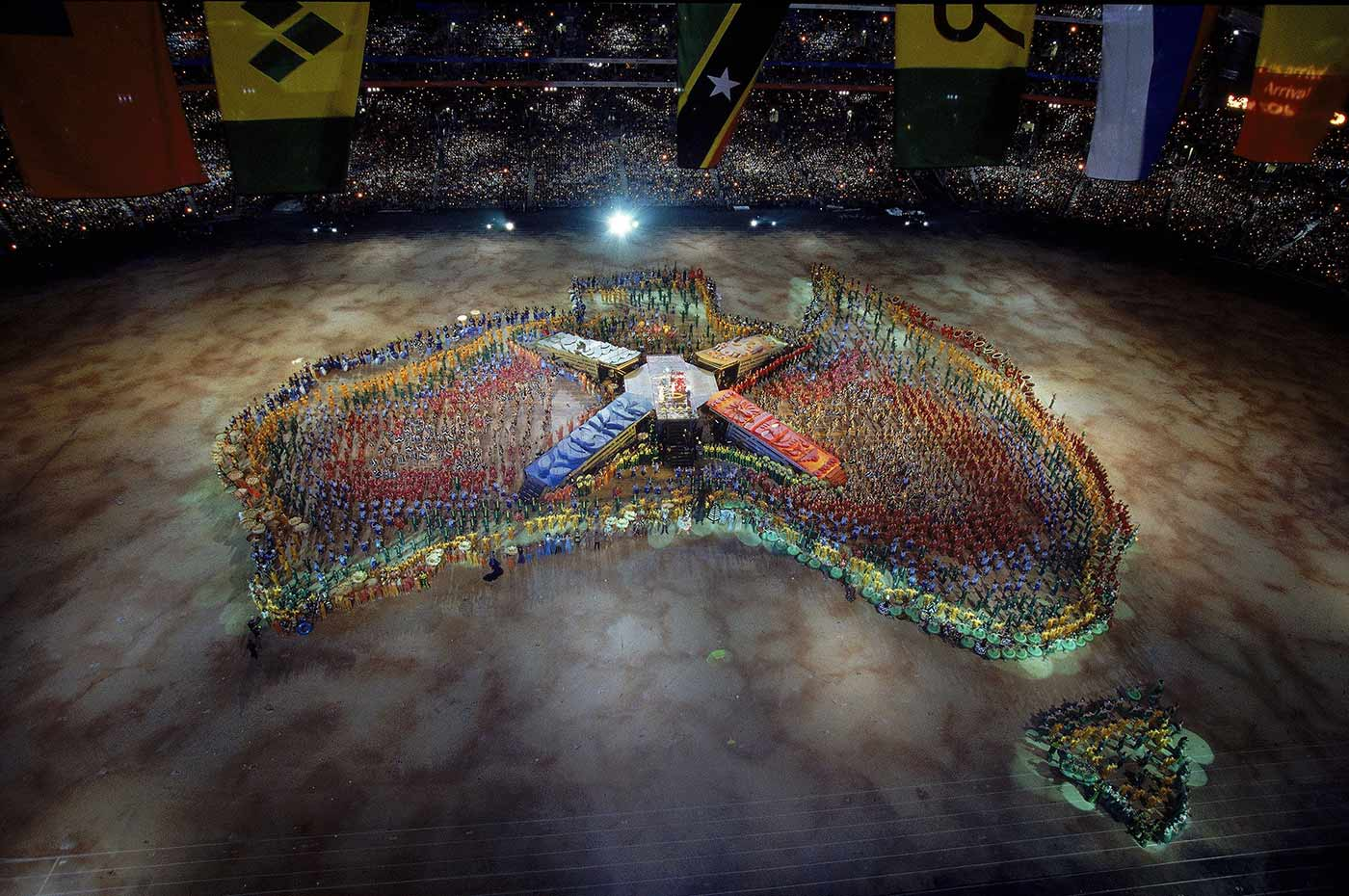 Hundreds of performers use their bodies to create a multi-coloured map of Australia in the centre of a stadium.