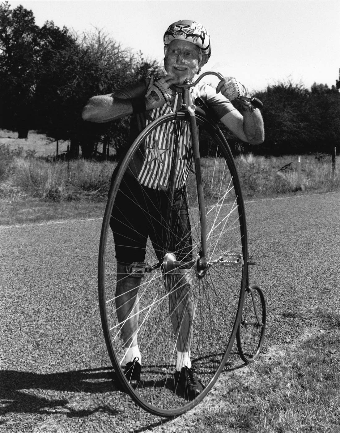 Black and white photograph of a man standing beside a penny-farthing bicycle. The man, who wears a helmet and has zinc cream across his cheeks, rests his head on the handlebars. He wears cycling gloves, shorts and a shirt with stars and stripes at the front. - click to view larger image