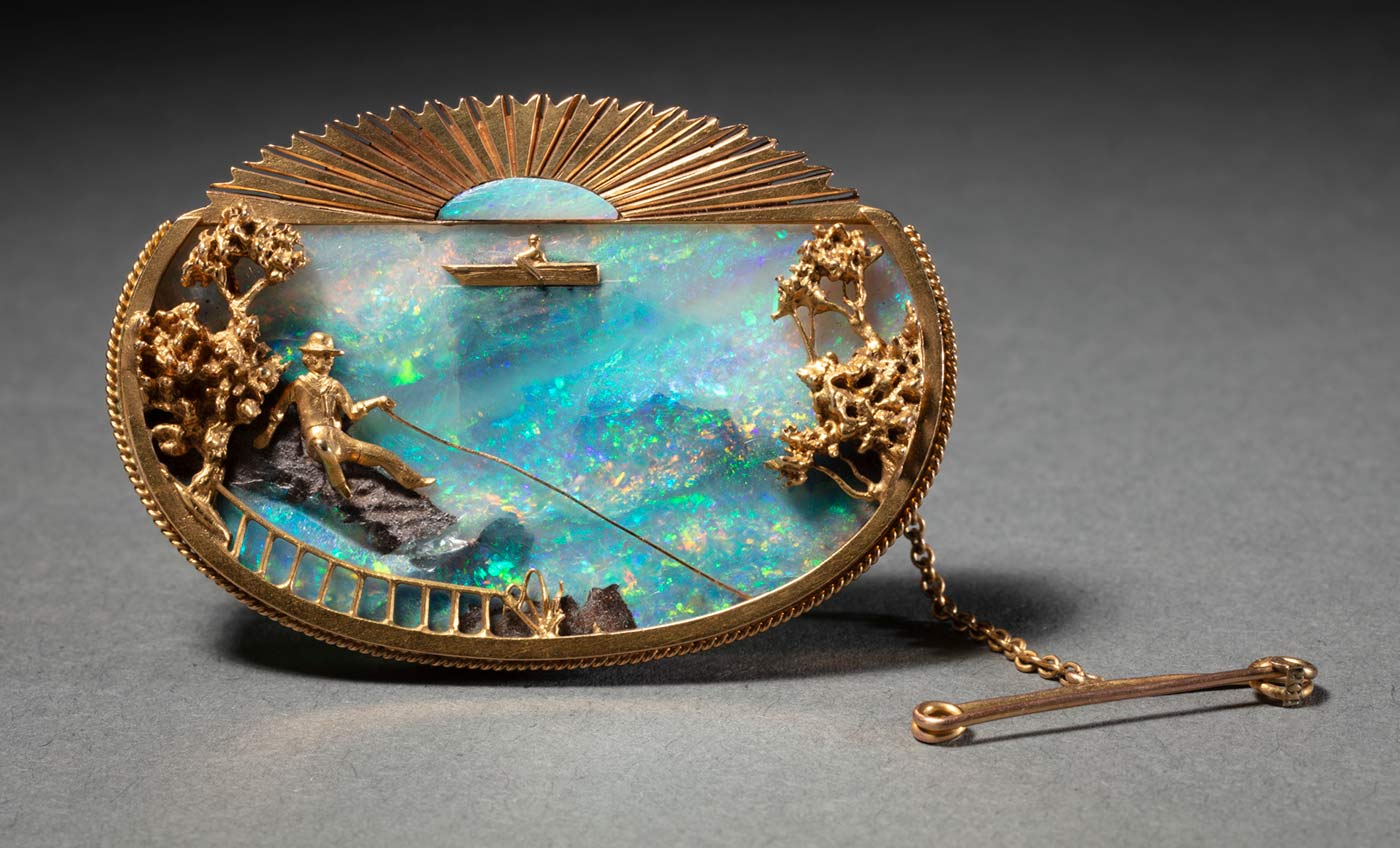 A gold oval brooch set with a blue opal and depicting a man sitting on a rock fishing in the foreground with trees on either side and a fence. There is a boat in the background and a sun motif at the top. - click to view larger image