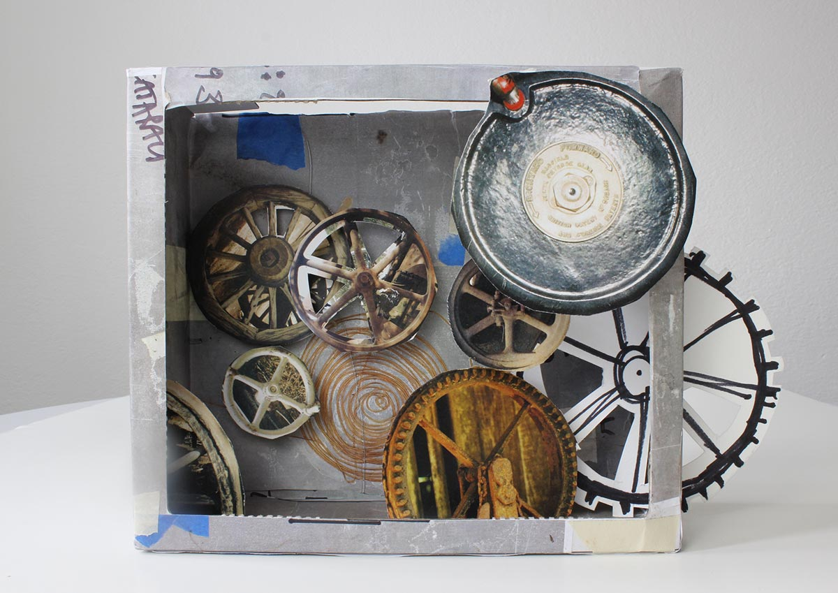 Diorama constructed from cardboard and various other materials. The interior of the box features cut-out colour images of round mechanical objects.