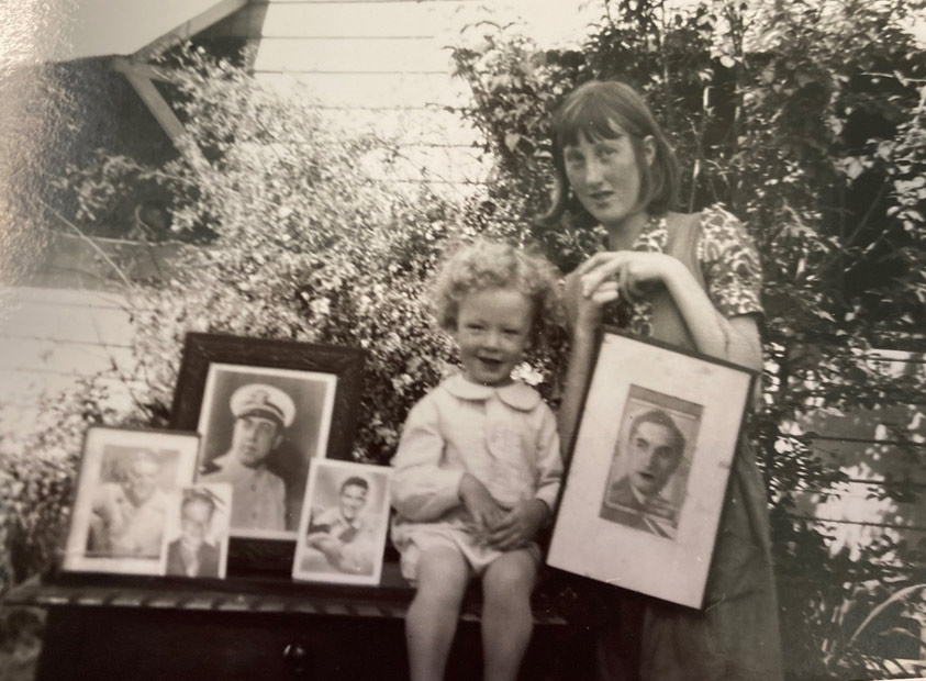 A black and white photograph of a young child seated next to a woman standing, both surrounded by framed photograph portraits of a man.