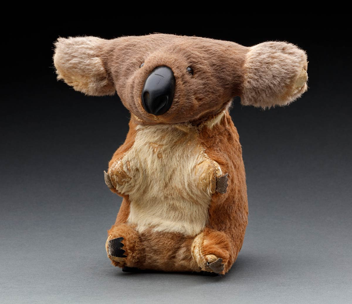 A toy Koala made of grey and brown kangaroo fur. It has small black plastic eyes, and black leather for the nose and claws. There are a number of areas across the toy where the fur is missing. - click to view larger image