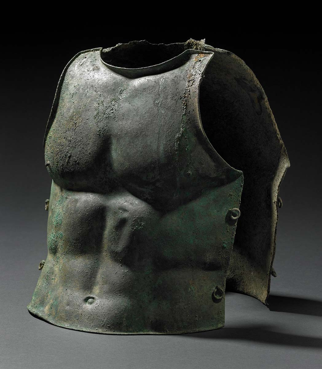 Body armour cast in the form of a man's torso with eyelets for threading on both sides. - click to view larger image