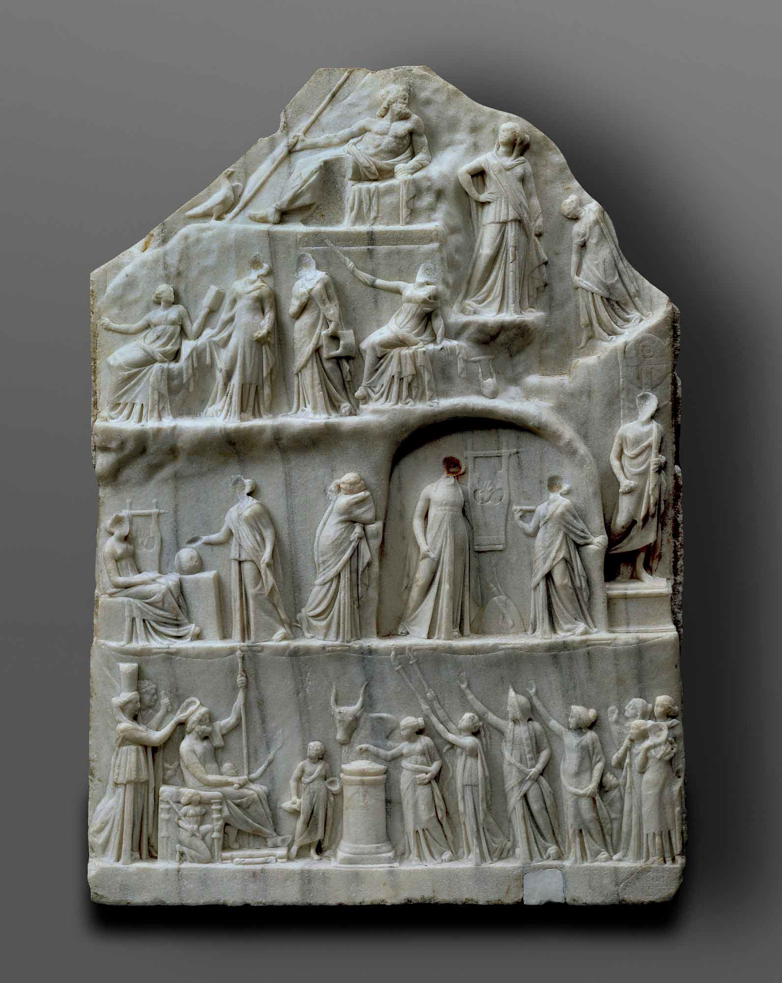 A marble block with a relief design and using a linear perspective to represent multiple figures along four rows, the top featuring a single man reclining. - click to view larger image