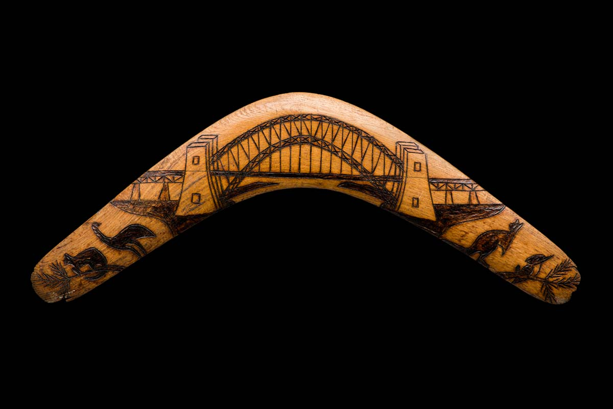 A symmetrical timber boomerang featuring, on the obverse, a pokerwork image of the Sydney Harbour Bridge, flanked on both sides by images of animals which include; (from left to right) a possum, an emu, a kangaroo and a kookaburra on a branch. - click to view larger image