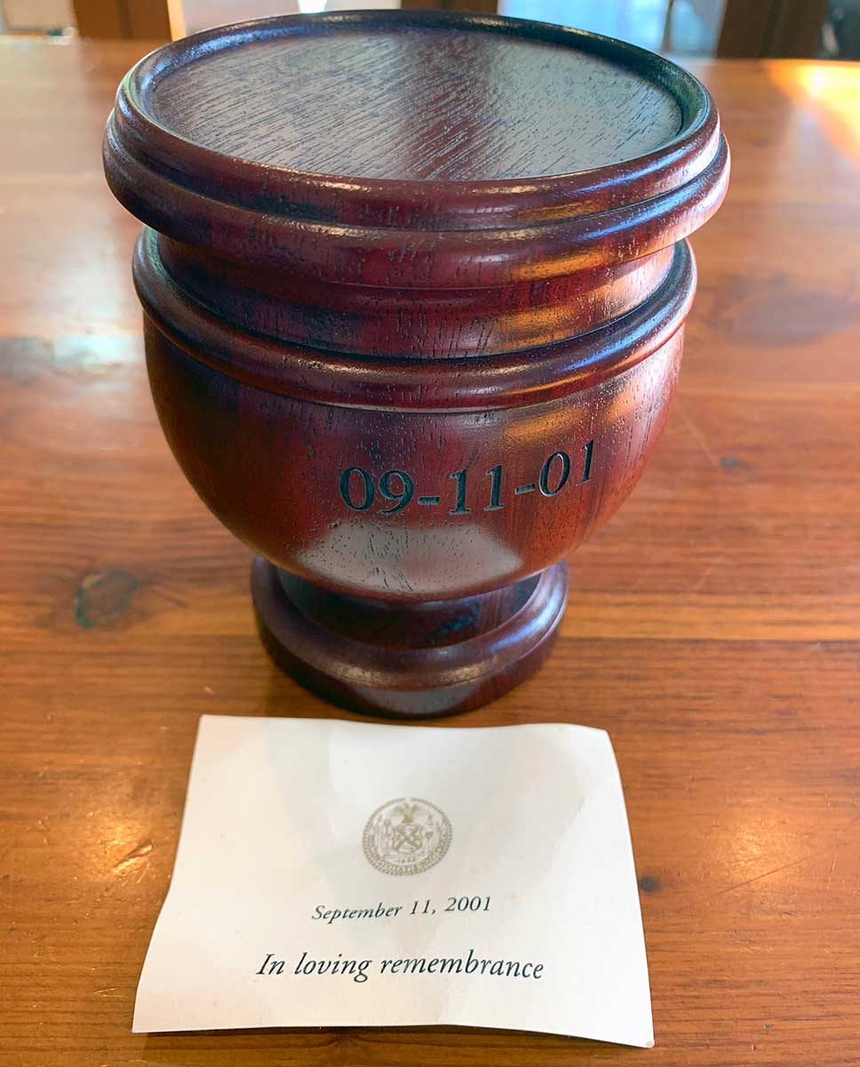 Small carved timber urn with the date 09-11-01 sitting on a timber surface. In front of the urn is a white card which says 'September 11 2001. In loving remembrance'. - click to view larger image