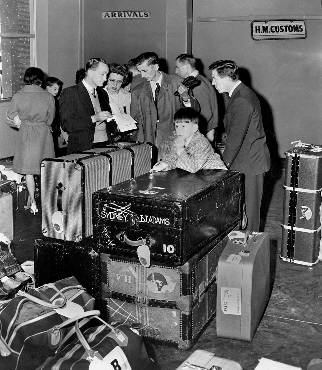 A group of people are standing around luggage. There is an 'ARRIVAL' sign and 'H.M customs' signs on the wall. - click to view larger image