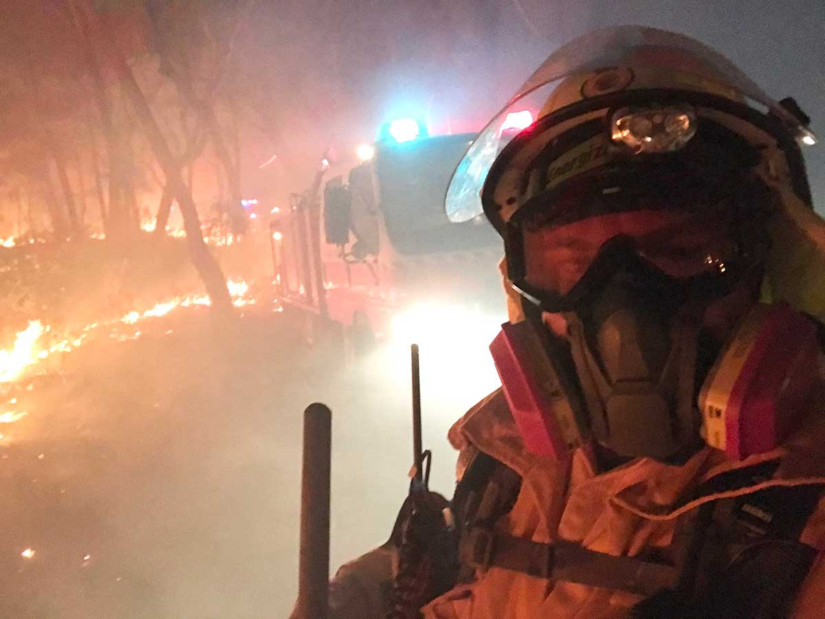 A firefighter is surrounded by a raging bushfire. - click to view larger image