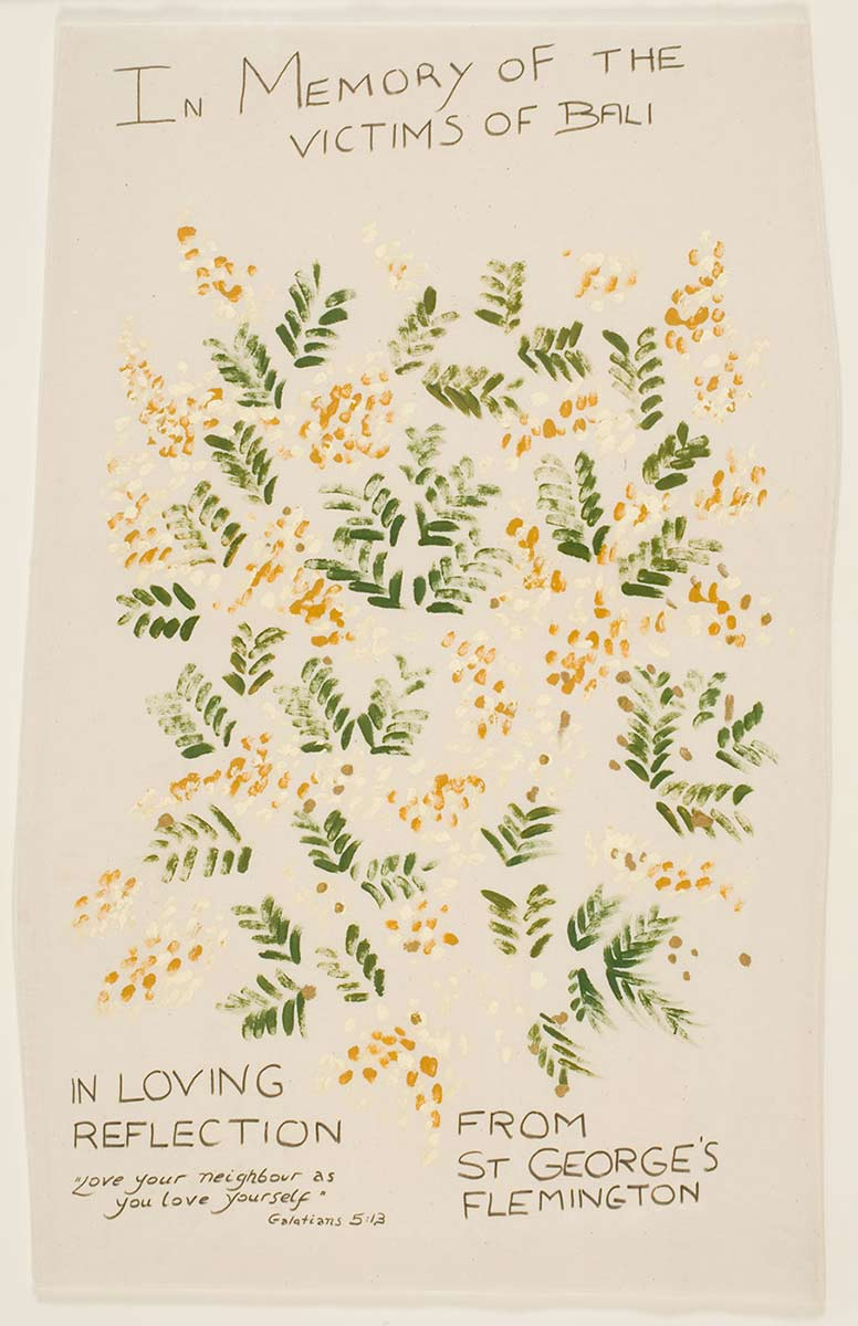 Linen fabric with green and gold wattle sprays screen-printed across the middle section. 'In Memory of the Victims of Bali' is handwritten across the top. 'In Loving Reflection, from St George's, Flemington' is printed at the bottom, along with a short bible verse. - click to view larger image