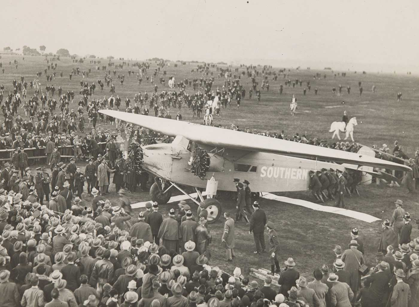 Black and white photo of a large crowd gathering around an air craft. - click to view larger image
