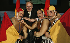 Senator the Hon Rod Kemp surrounded by Terry, Sandy and Barry who are dressed in surf lifesaving costumes and holding red and yellow flags.