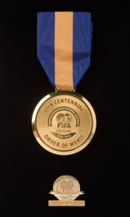 A gold metal disc with a central logo and the text 'INTERNATIONALE DE FOOTBALL ASSOCIATION / FIFA / 100 YEARS / 1904-2004'. The medal hands from a blue and yellow vertically striped ribbon. A small circullar gold finished lapel pin sits below the main medal. Both appear on a black backdrop.