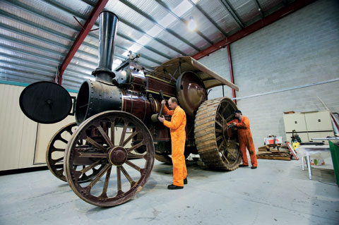 The Fowler steam engine towers over Peter Bucke and Ian Cramer as they perform maintenance work