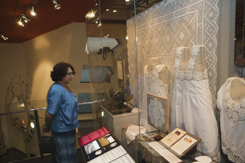 A woman stands looking into a case which contains a crocheted table cloth and doily and white undergarments with crocheted trims.