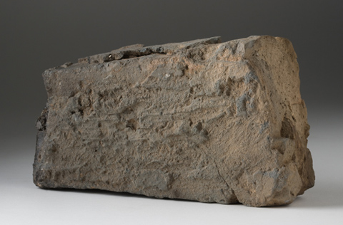 A roughly rectangular brick, greyish brown in colour, with irregular substances on the surface.