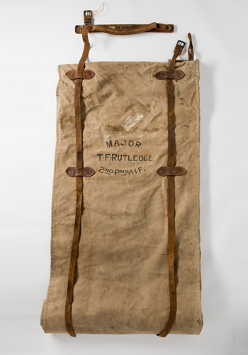 Fawn-coloured canvas bed roll with brown leather straps. The words 'MAJOR. / T. F. RUTLEDGE. / 2ND. PNR. [Pioneer] A.I.F.' are painted on the canvas between the leather strapping. The swag includes the remains of a railway baggage label.