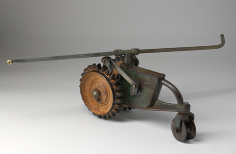 Tractor-like 'walking' lawn sprinkler with a green painted cast metal chassis with a grooved wheel at the front and a pair of larger cast metal wheels on the back axle. A rotating copper tube sprinkler arm is attached horizontally to the top of the body at a brass T-piece.
