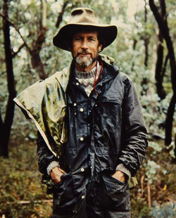 Portrait of a man standing in a forest wearing a hat and waterproof jacket.