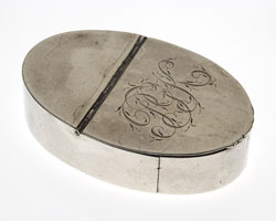 Oval-shaped silver snuffbox with intials PGK engraved on top.