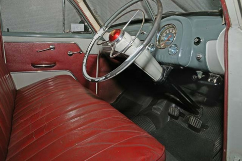 Interior view of a car showing a blue-grey body with red bench seat and right hand side drive.