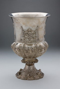 An ornate sterling silver cup with a central engraving and coat of arms.