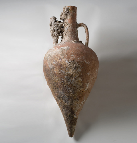 A pale orange clay vessel with two handles extending from the neck to the body. Encrustation and cracks appear on the vessel, which narrows at the base.