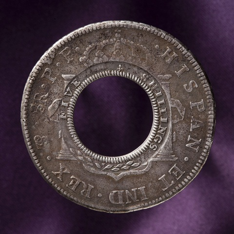 Circular coin with a hole at the centre. 'HISPAN ET IND REX' is stamped around the outer rim, with 'FIVE SHILLINGS' on the inner rim.
