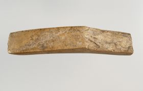 Long adze blade, 14.5cm long, and made of a yellowish limestone. The upper and lower surfaces of the sharp edge are rectangular.
