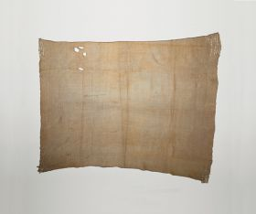 Hand-woven cloak of brown-beige colour made of flax, with remnants of dog fur strips on all four corners.